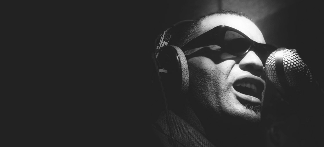 Ray Charles in the studio wearing headphones and sunglasses next to a microphone