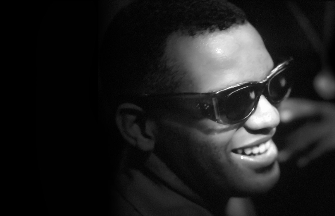 Ray Charles smiling over a black background, wearing sunglasses