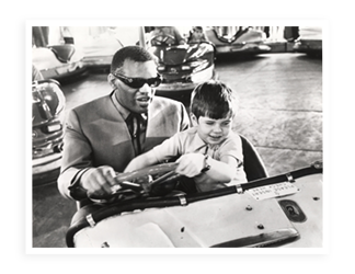 Ray Charles and a child in a bumper car from the movie, Ballad in Blue