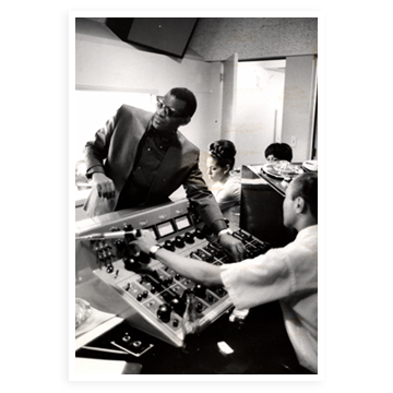 Ray Charles leaning over a studio mixer