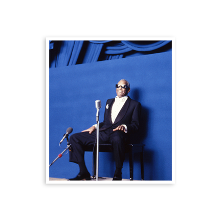 Ray Charles at the Kennedy Center Honors sitting in front of blue background