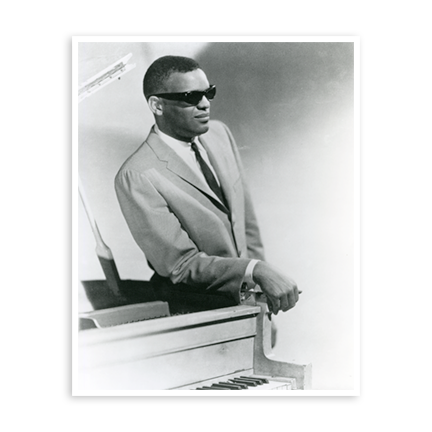Ray Charles standing and leaning on the piano in his trademark sunglasses