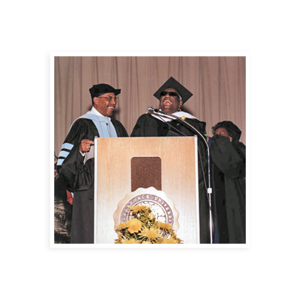 Ray Charles at the podium in a graduation cap and gown