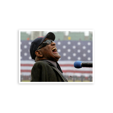 Ray Charles wearing a baseball cap and his trademark sunglasses singing the National Anthem