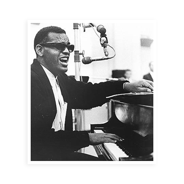 Ray Charles singing into a mic and playing piano