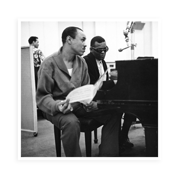 Joe Adams and Ray Charles sitting at the piano