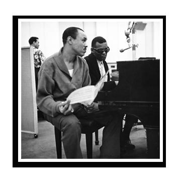 Joe Adams and Ray Charles sitting at the piano
