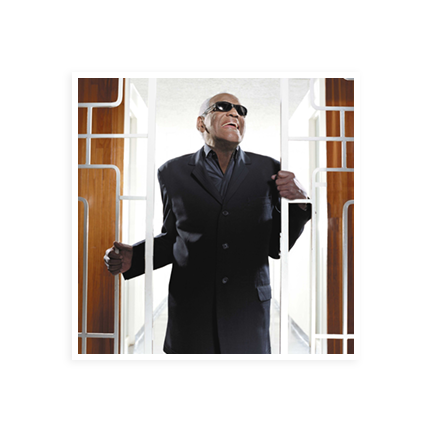 Ray Charles wearing his trademark sunglasses standing in front of a white gate