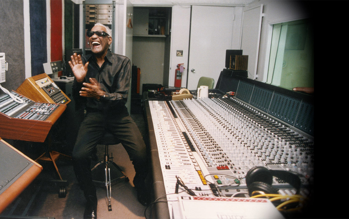 Ray Charles in studio engineering room next to sound equipment and mixer