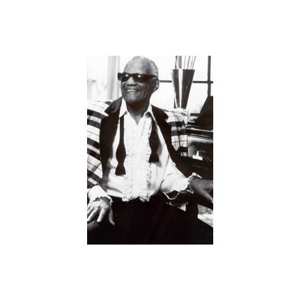 Ray Charles sitting at the piano and smiling